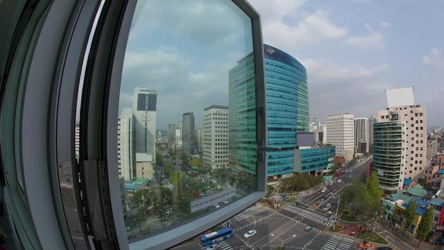 路上で激しい車の通行がある街のパノラマの広角ショット。窓から韓国のソウルまでの眺め