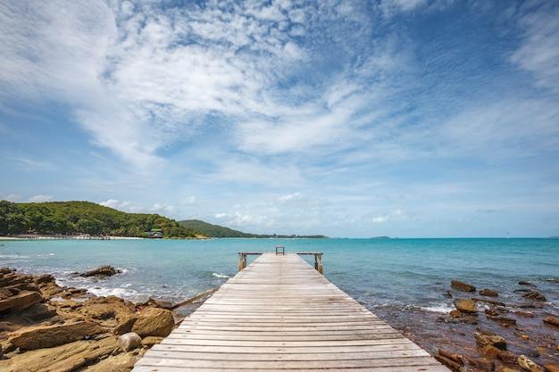 Широкоугольный снимок пристани к морю с ярко-голубым небом и облаками в расслабляющий летний день