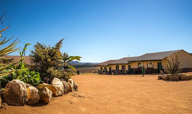Широкоугольный снимок домов, построенных на сухом поле рядом с несколькими растениями