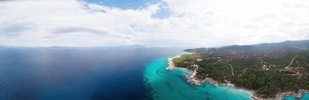Широкоугольный снимок скалистого побережья эгейского моря с зеленью вокруг, кустами и деревьями, холмами и горами, голубой водой с волнами, видом с дрона греция