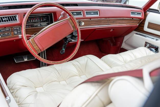 Широкоугольный снимок салона автомобиля, включая красный руль и белые сиденья.