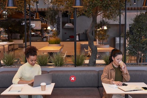 사회적 거리, 코비드 안전 개념, 복사 공간이 있는 카페 테이블에서 일하는 동안 노트북을 사용하는 두 젊은 여성의 광각 사진