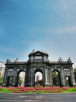 Wide angle shot of the puerta de alcala monument in madrid, spain under a clear blue sky