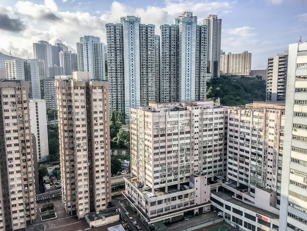 Wide angle shot of several buildings of hong kong built next to each other during daytime