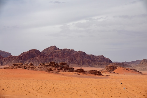 Wide angle shot of several large cliffs on a desert under a cloudy sky