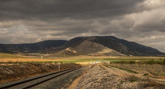 Colpo grandangolare dei binari del treno che vanno verso una montagna sotto un cielo nuvoloso