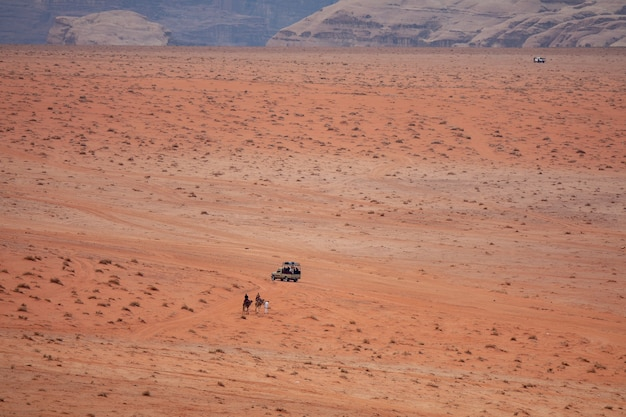 Wide angle shot of two people on camels approaching a car in a desert