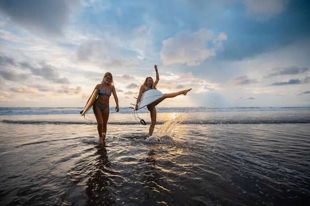Wide angle shot of two women standing on the beach during a sunset