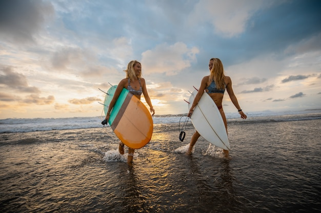 Wide angle shot of two women walking on the beach with surfing boards