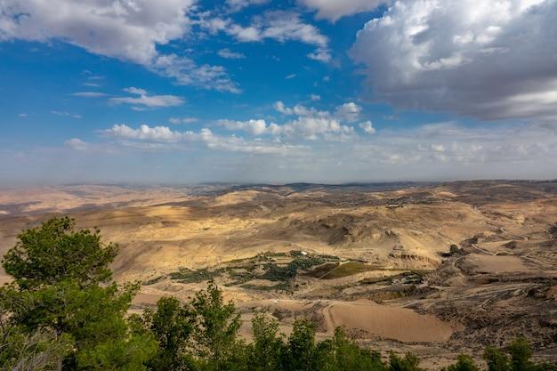 Colpo grandangolare di una valle di alberi e montagne sotto un cielo pieno di nuvole