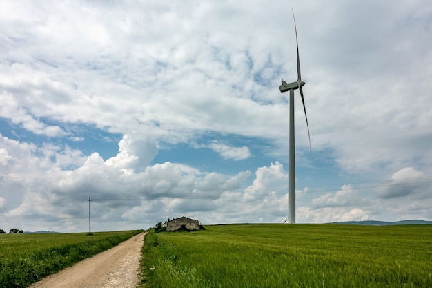 Wide angle shot of a wind fan next to a green field under a cloudy sky