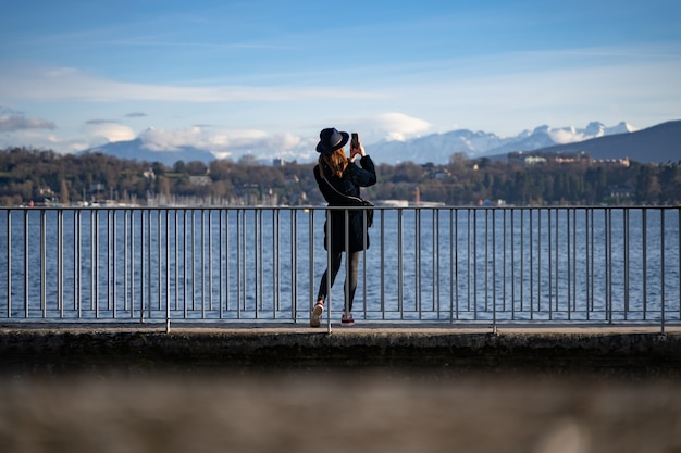 Wide angle shot of a woman standing in front of the water and taking pictures of mountains
