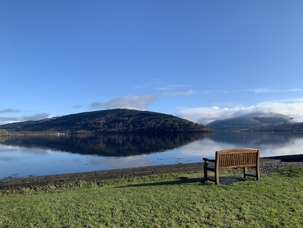 Wide angle shot of a wooden bench on a green field in front of water and a mountain