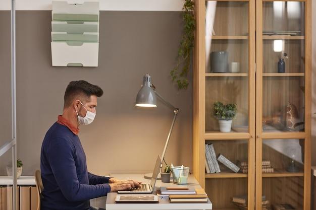 マスクを着用し、オフィスのデスクで作業中にラップトップを使用して、スペースをコピーする現代の成熟した男性の広角側面図