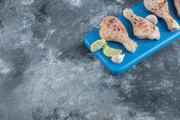 Angolo ampio. cosce di pollo crude piccanti sul bordo di legno blu.
