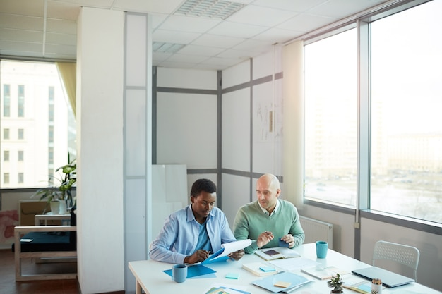 Wide angle view of african-american young man consulting with mature manager while sitting at table in office, copy space