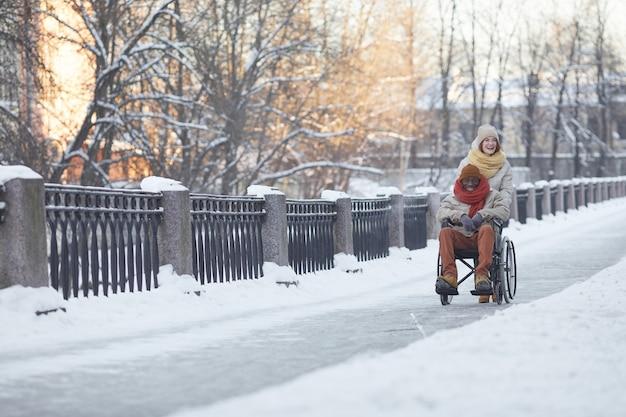 Широкоугольный вид афроамериканца, использующего инвалидную коляску, развлекающегося на открытом воздухе зимой с помощью улыбающейся молодой женщины, копией пространства