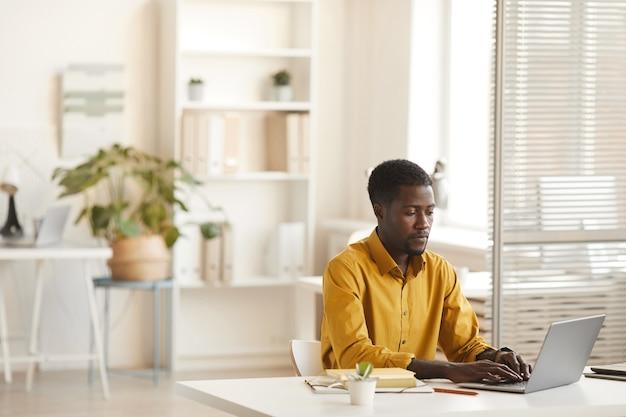 최소한의 사무실 인테리어, 복사 공간에 책상에서 작업하는 동안 노트북을 사용하는 현대 아프리카 계 미국인 남자의 넓은 각도보기