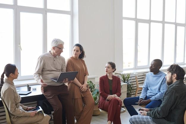 Широкоугольный взгляд на современную разнообразную бизнес-команду, сидящую в кругу во время стратегической встречи, фокус на разговоре старшего бизнесмена, копирование пространства