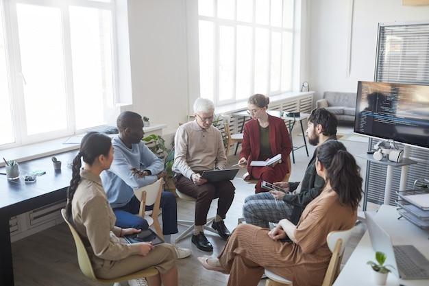 Широкоугольный взгляд на современную разнообразную бизнес-команду, сидящую в кругу во время стратегической встречи, сосредоточение внимания на старшем мужчине в центре, копировальное пространство