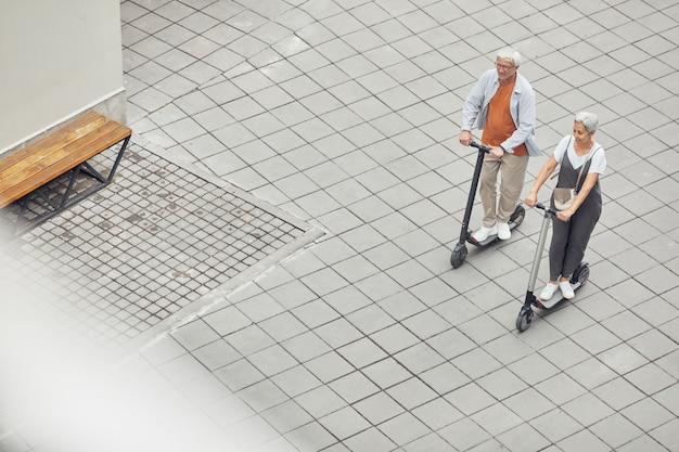 Широкоугольный вид на современную зрелую пару, катающуюся на электрических скутерах в парке на плиточном фоне, копировальное пространство