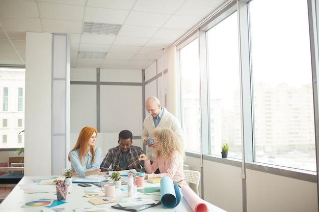 現代の白いオフィス、コピースペースのテーブルでの会議中に創造的なプロジェクトを議論する多様なビジネスチームの広角ビュー