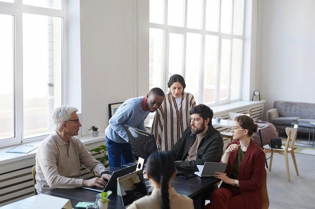 Широкий угол обзора на разнообразную группу деловых людей, встречающихся в офисе и использующих компьютер во время обсуждения проекта, копирование пространства