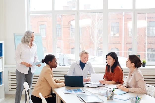 会議室での会議中に窓に対してテーブルに座ってプロジェクトを議論しているビジネスウーマンの多様なグループでの広角ビュー