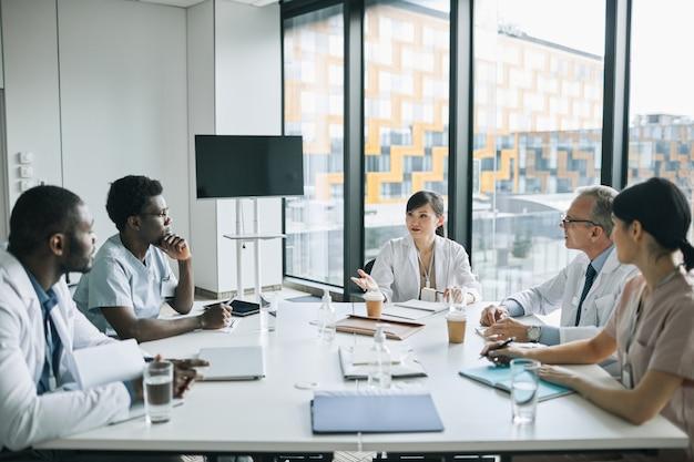 의학 세미나 중 회의실의 회의 테이블에 앉아 있는 다양한 의사 그룹의 넓은 각도 보기, 복사 공간