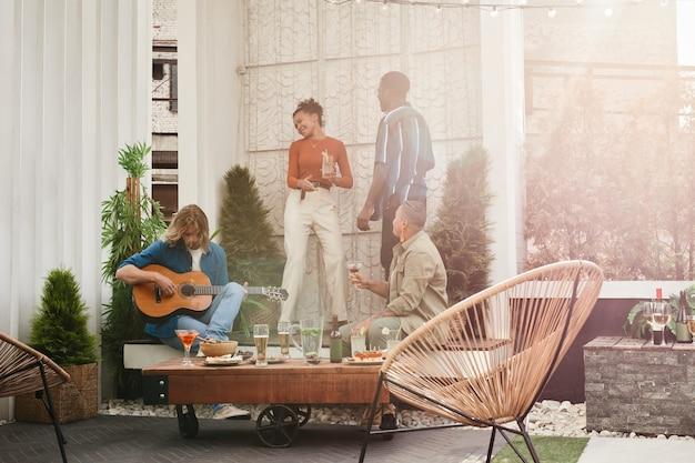 屋上での野外パーティー中に踊る友人の多様なグループの広角ビュー、日光の下でギターを弾く若い男、コピースペース