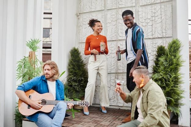 若い男がギターを弾く、屋上での野外パーティー中に踊る友人の多様なグループの広角ビュー