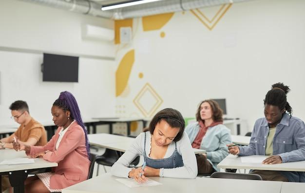 正面の若いアフリカ系アメリカ人女性に焦点を当てた、学校のクラスの机に座っている学生の多様なグループの広角ビュー、コピースペース