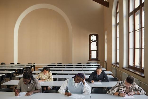 학교 강당의 책상에 앉아 시험을 보는 다양한 학생들의 넓은 각도 보기, 복사 공간