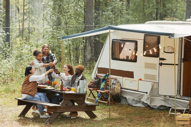 屋外でピクニックを楽しみながらビール瓶をチリンと鳴らす若者の多様なグループの広角ビュー...