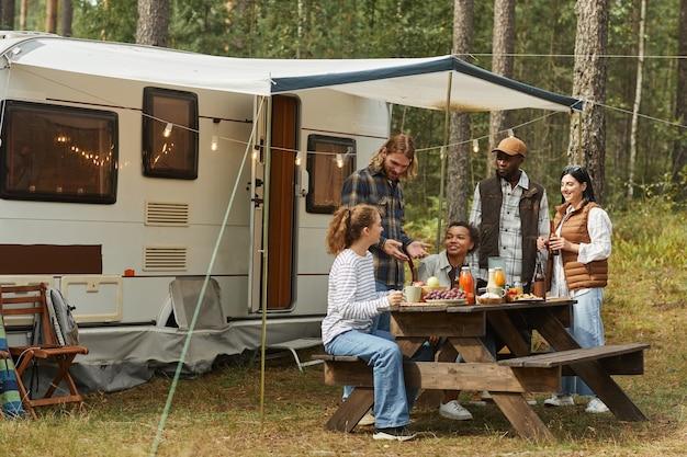 トレーラーでキャンプしながら屋外でピクニックを楽しんでいる若者の多様なグループの広角ビュー...