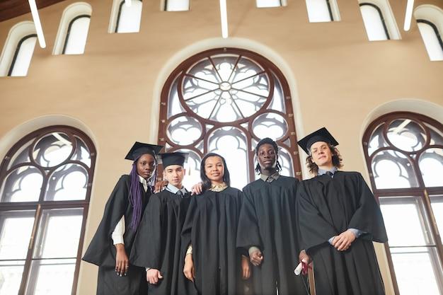 고전적인 학교 강당의 화려한 창문 옆에 서서 졸업 가운을 입은 다양한 젊은이들의 넓은 각도 보기, 복사 공간