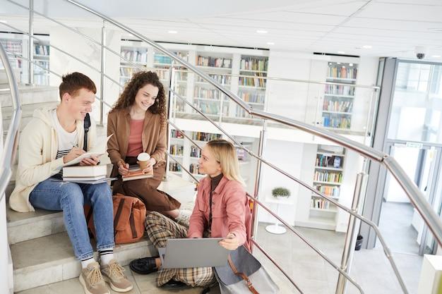 Широкоугольный вид на группу студентов, сидящих на лестнице в колледже и использующих ноутбук во время работы над домашним заданием,