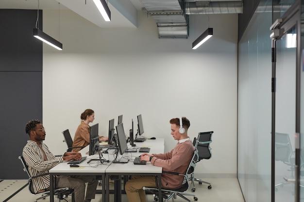 Широкоугольный вид на группу студентов, использующих компьютеры в школьной библиотеке или ит-лаборатории, место для копирования