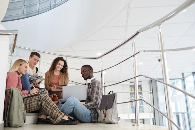 Широкий угол обзора многонациональной группы студентов, сидящих на лестнице в колледже и использующих ноутбук во время работы над домашним заданием.