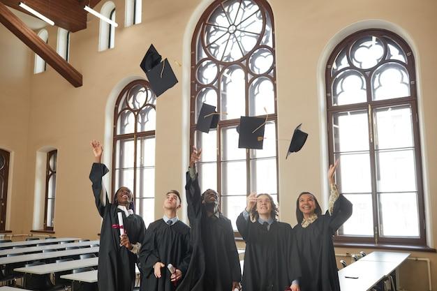 클래식 학교 강당에서 실내 졸업식 중 모자를 공중에 던지는 다민족 젊은이들의 넓은 각도 보기, 복사 공간