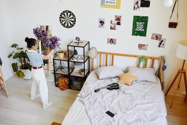 Широкоугольный вид на интерьер комнаты подростка с девушкой, танцующей с помпонами, копией пространства
