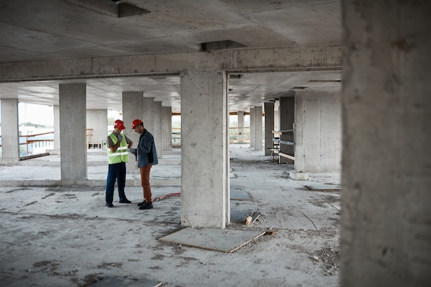 建設現場に立ってプロジェクトを話し合う2つの建築請負業者の広角ビュー、コピースペース