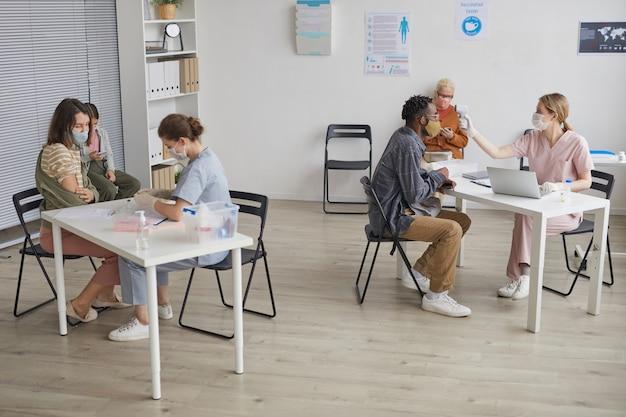 Широкоугольный вид на двух врачей, консультирующих пациентов в центре вакцинации или клинике, копировальное пространство