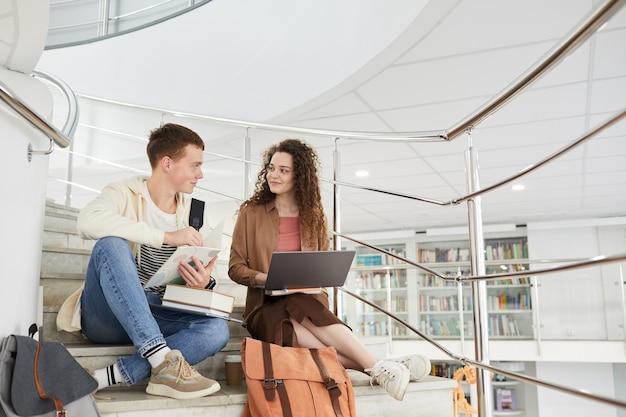 Широкоугольный вид на двух студентов, сидящих на лестнице в библиотеке колледжа и использующих ноутбук во время работы над домашним заданием,
