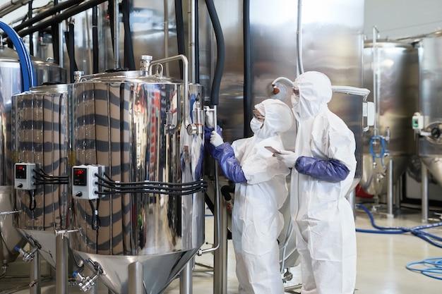 현대 화학 공장에서 생산을 검사하는 동안 보호복을 입은 두 명의 작업자에 대한 광각 보기, 복사 공간