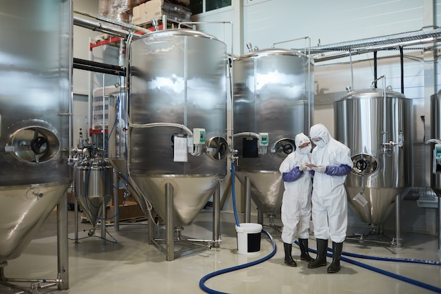 현대 화학 공장에서 디지털 태블릿을 사용하는 동안 보호복을 입은 두 작업자의 넓은 각도 보기, 복사 공간