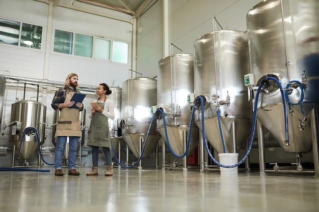 醸造所のワークショップ、コピースペースに立っている間エプロンを身に着けている2人の若い労働者の広角ビュー
