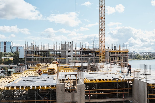 Wide angle view at construction site with unfinished residential buildings against blue sky, copy space