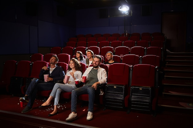 Wide angle view at group of friends watching movie in cinema while enjoying private viewing in empty hall, copy space