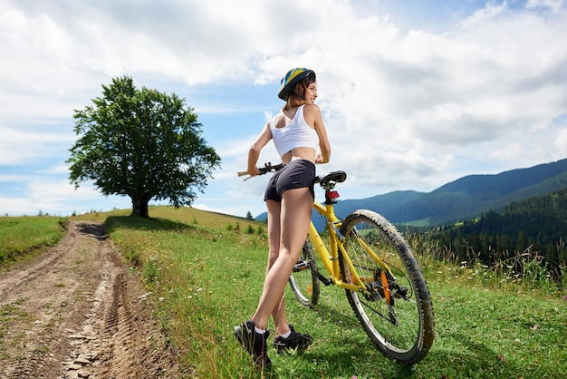 山の田舎道で黄色の自転車に乗って魅力的な女性サイクリストの広角ビュー。大きな木と背景に曇り空。アウトドアスポーツ活動